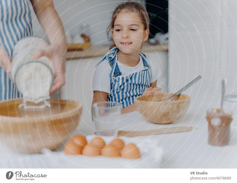 Neugieriges kleines Mädchen schaut, wie Mama Teig für Gebäck vorbereitet, lernt zu kochen, bekommt kulinarische Erfahrung, trägt Schürze. Gesichtslose Frau fügt Mehl in Schüssel mit anderen Zutaten, Pose in der Küche mit Kind