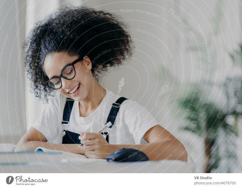 Glückliche afroamerikanische Studentin schreibt Informationen auf, bereitet sich auf Prüfungen vor, sitzt im Coworking Space, hat lockiges dunkles Haar, trägt eine optische Brille, weißes T-Shirt und Latzhose, studiert in einem geräumigen Zimmer