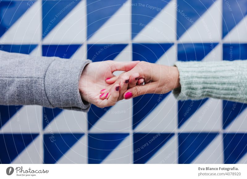 Nahaufnahme von zwei Frauen, die Hände gegen blaue und weiße Fliesen halten. Freundschaft oder lgtbi Konzept Händchenhalten Freunde Kacheln lesbisch Liebe Porto