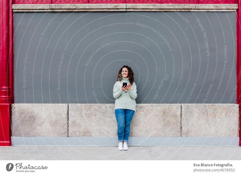 Junge kaukasische Frau, die ein Mobiltelefon im Freien in der Stadt benutzt. Technologie und Lebensstil Handy Großstadt urban Technik & Technologie Texten