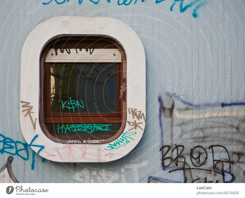 Fenster im Retro-Look mit weiß-braunem Rahmen auf hellblauer Wand überhäuft mit Graffiti Fensterscheibe Fensterladen Fensterscheiben retro retro-stil