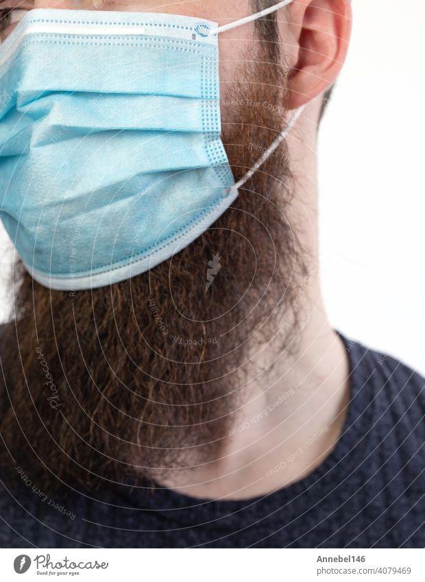 Kaukasischer junger bärtiger erwachsener Mann, der eine schützende oder chirurgische Maske trägt, um Verschmutzung und ansteckende Viren und Krankheiten zu vermeiden, isoliert auf weißem Hintergrund, Covid-19, Coronavirus, Gesundheit, Bart, Epidemiekonzept