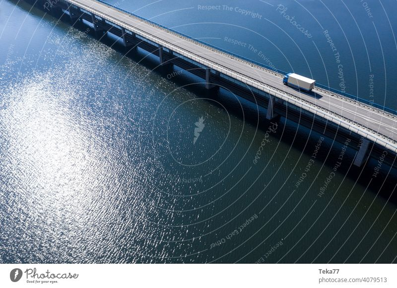 ein LKW fährt auf einer Brücke im Wasser Lastwagen Lkw-Fahren Zukunft zukünftiger Transport MEER See von oben Sonne moderner TransportModell-LKW Raserei