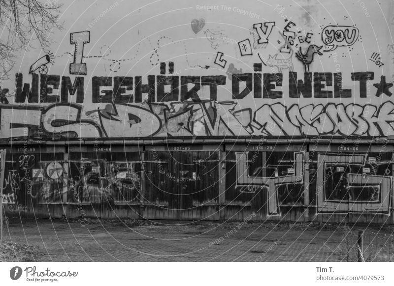 """ein Graffiti auf der Fassade über den Garagen """"Wem gehört die Welt"""" Weißensee Berlin Garagentor old Menschenleer Außenaufnahme Wand Einfahrt Tag Tor Gebäude"""