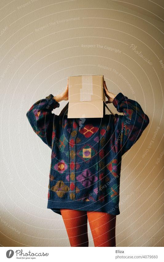 Frau in bunter Kleidung mit einem Karton auf dem Kopf Kiste verschicken bestellen anonym verstecken genervt Paket Schachtel Verpackung Pappkarton Pullover dsgvo