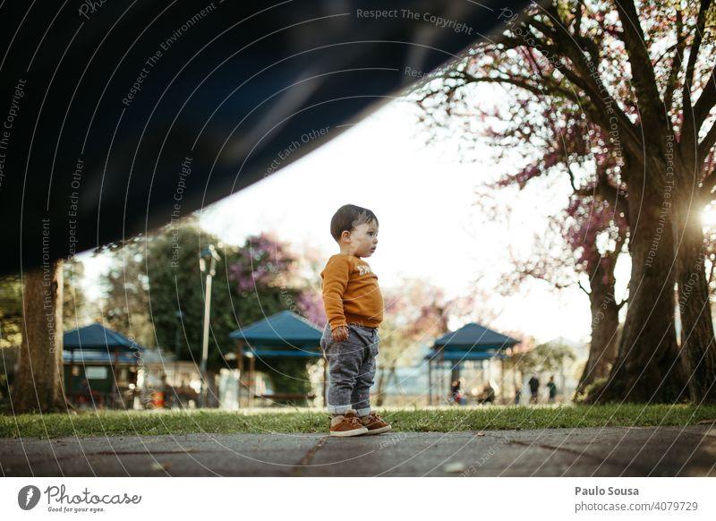 Kind stehend auf dem Spielplatz Junge 1-3 Jahre Kaukasier Stehen Neugier farbenfroh Frühling Frühlingsfarbe Natur authentisch Außenaufnahme Farbfoto Kindheit