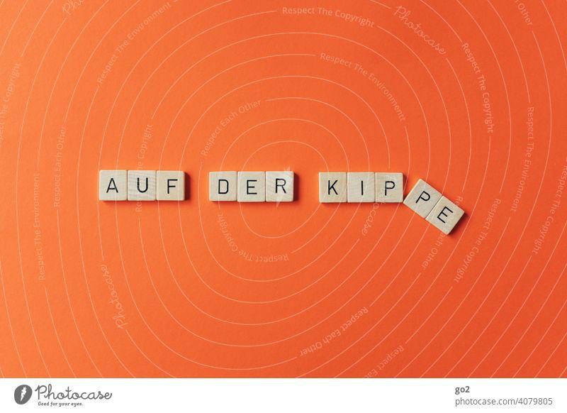 Auf der Kippe auf der kippe Buchstaben Scrabble Redewendung Schriftzeichen Typographie unsicher Unsicherheit umfallen Entscheidung Text Missgeschick pech