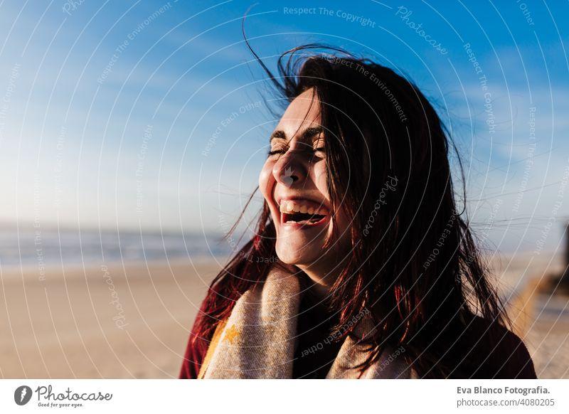 glückliche Frau, die Spaß am Strand an einem windigen Tag bei Sonnenuntergang. Urlaub und Spaß Konzept Lachen Glück Fröhlichkeit sich[Akk] entspannen Kaukasier