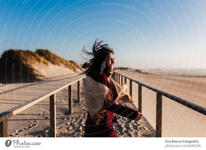 glückliche Frau, die Spaß am Strand an einem windigen Tag bei Sonnenuntergang. Urlaub und Spaß Konzept rennen Lachen Glück Fröhlichkeit sich[Akk] entspannen