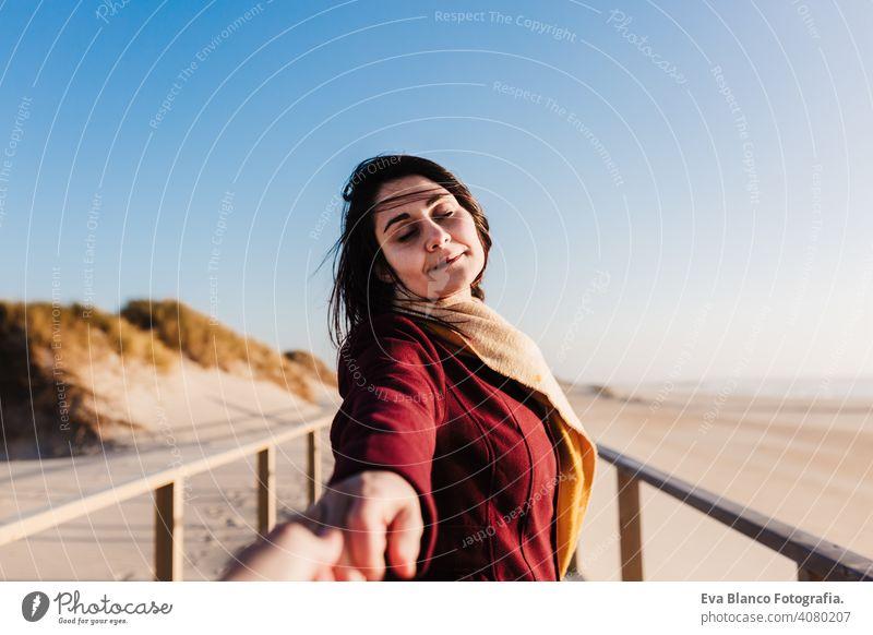 junge kaukasische Frau mit geschlossenen Augen am Strand bei Sonnenuntergang entspannen. Halten Sie die Hände mit der Kamera, folgen Sie mir. Urlaub und Entspannung Konzept