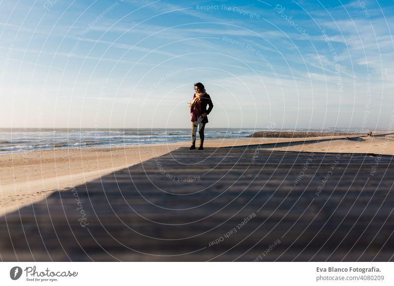 junge kaukasische Frau am Strand bei Sonnenuntergang entspannen. zu Fuß durch hölzerne Passage oder Landebahn. Urlaub und Entspannung Konzept laufen entspannend