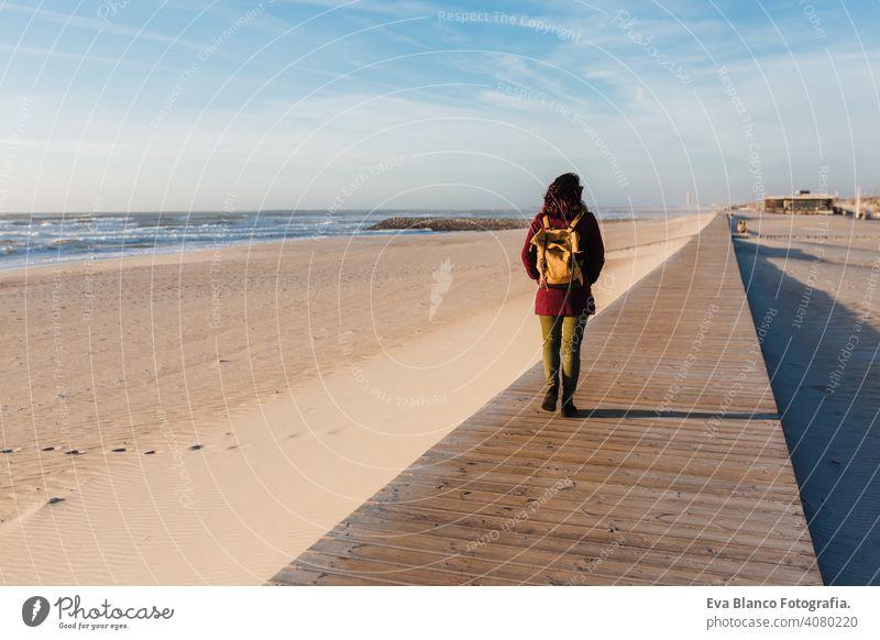 Backpacker junge kaukasische Frau am Strand bei Sonnenuntergang entspannen. zu Fuß durch hölzerne Passage oder Landebahn. Urlaub und Entspannung Konzept laufen