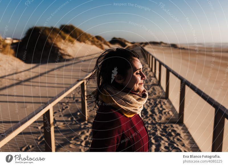junge kaukasische Frau mit geschlossenen Augen entspannt am Strand bei Sonnenuntergang. Urlaub und Entspannung Konzept sich[Akk] entspannen Kaukasier Feiertage