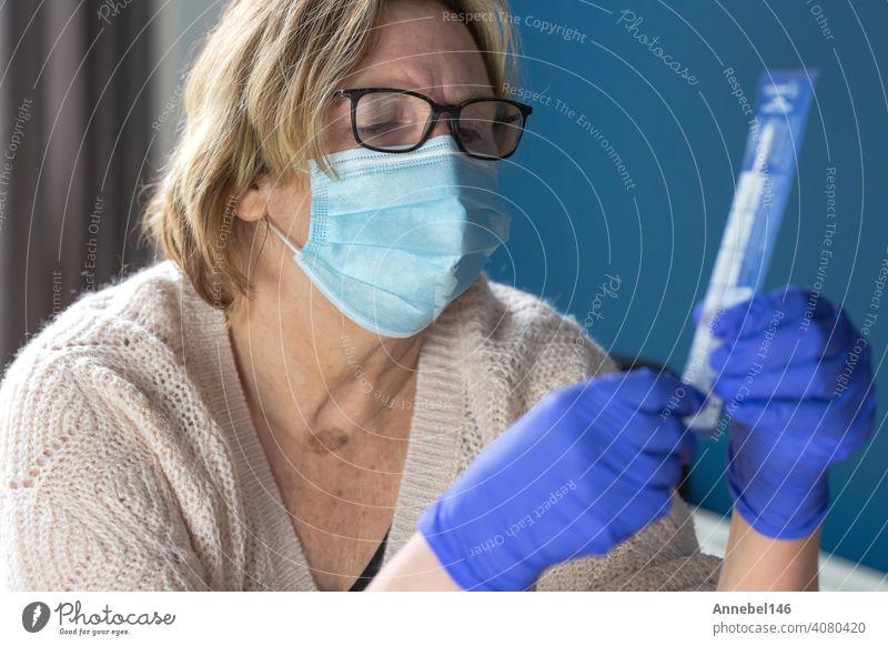 Ältere Frau studiert und macht den Selbsttest für Covid-19, Heimtestkit für Coronavirus Virus Gesundheit Bausatz Pandemie heimwärts Tupfer Seuche Krankheit