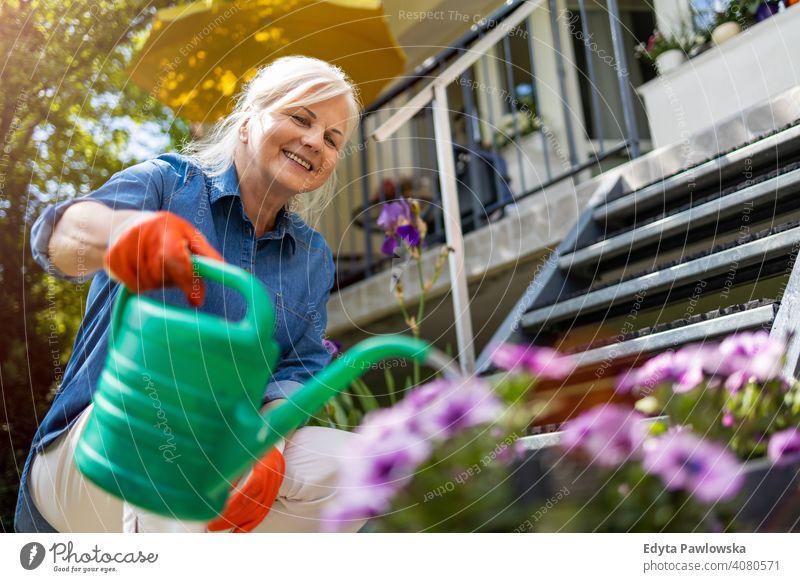 Ältere Frau bewässert Pflanzen in ihrem Garten Lächeln Glück genießend Positivität Vitalität Freude Selbstvertrauen Menschen Senior reif lässig Kaukasier älter