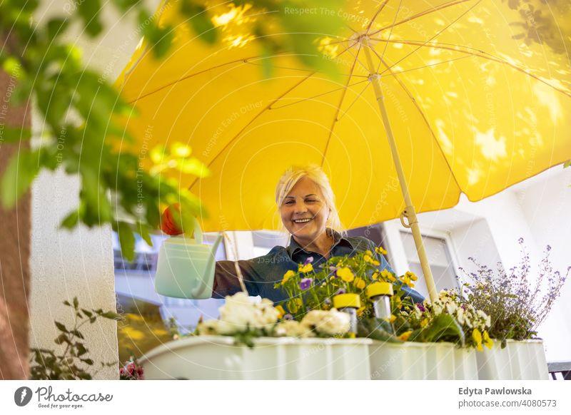 Seniorin, die sich um ihre Pflanzen auf dem Balkon kümmert Lächeln Glück genießend Positivität Vitalität Freude Selbstvertrauen Menschen Frau reif lässig