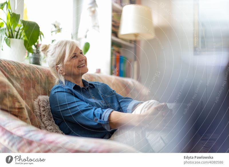 Schöne ältere Frau entspannt zu Hause Lächeln Glück genießend Positivität Vitalität Freude Selbstvertrauen Menschen Senior reif lässig Kaukasier heimwärts alt