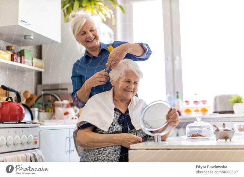 Frau schneidet ihrer älteren Mutter zu Hause die Haare Lächeln Glück Menschen Senior reif heimwärts alt häusliches Leben Großmutter Rentnerin Großeltern