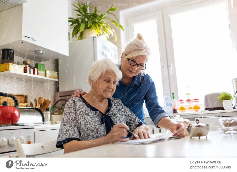 Ältere Frau hilft ältere Mutter mit Papierkram Wille Schriftstück Diskussion über schreibend Finanzen Geld Verwirrung lesen Küche heimisch Unterstützung