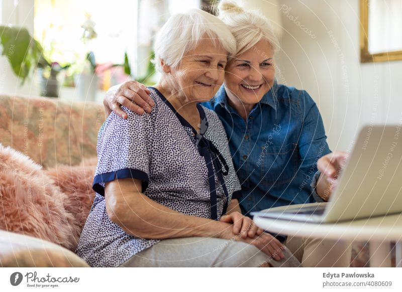 Reife Tochter bringt ihrer älteren Mutter den Umgang mit dem Laptop bei Computer zwei Personen Bonden Familie Liebe Zusammensein besuchen Eltern Freunde Art