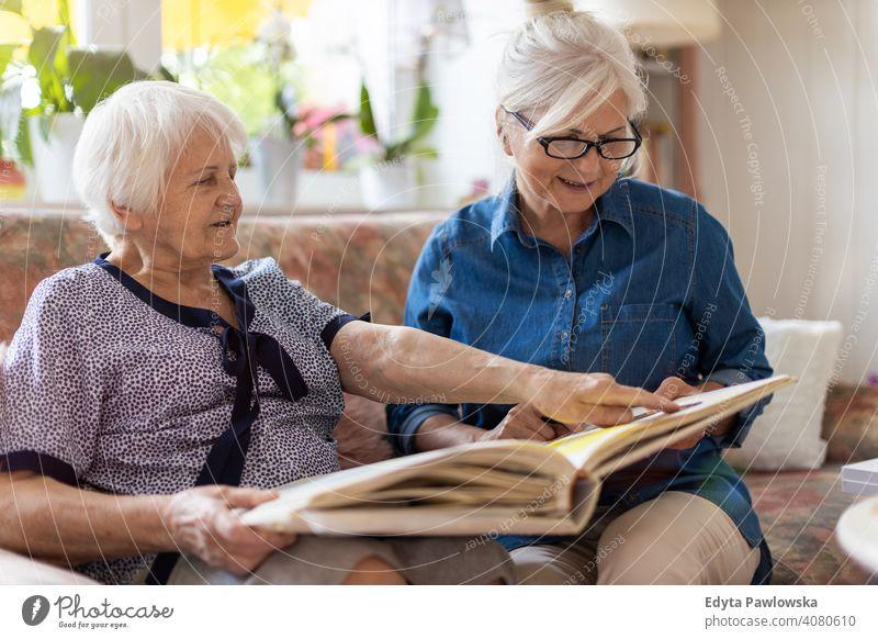 Ältere Frau und ihre erwachsene Tochter betrachten gemeinsam ein Fotoalbum auf der Couch im Wohnzimmer Sitzen Gedächtnis Erinnerungen Nostalgie Historie Fotos