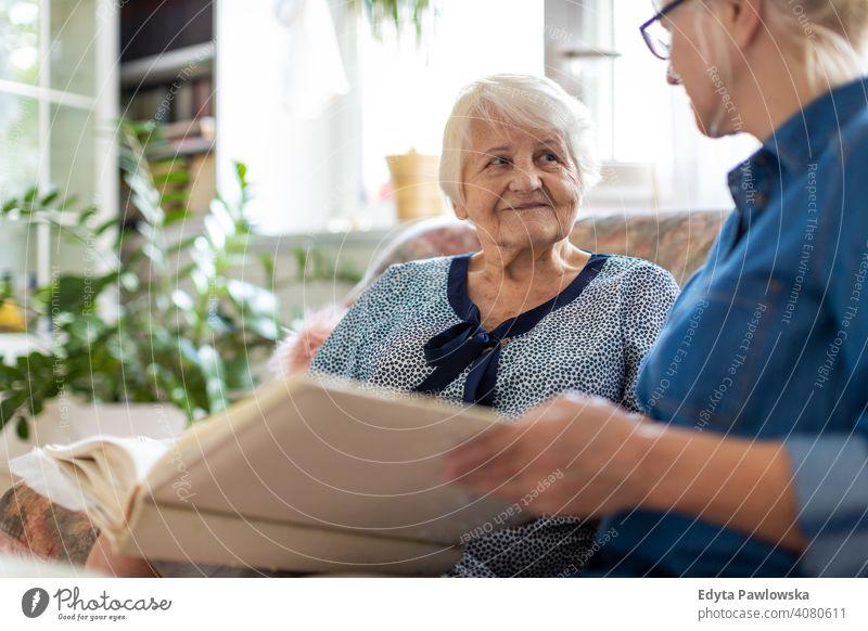 Oma zeigt ihrer Tochter Erinnerungen aus der Vergangenheit Sitzen Gedächtnis Nostalgie Historie Fotoalbum Fotos zeigend erinnern Bonden Zwei Personen Familie