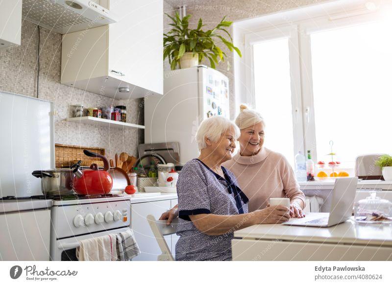 Erwachsene Tochter lehrt ihre ältere Mutter, den Laptop zu benutzen Computer Zwei Personen Bonden Familie Liebe Zusammensein besuchen Eltern Freunde freundlich