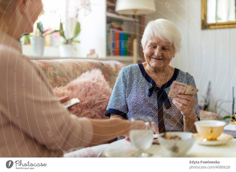 Ältere Frau und ihre erwachsene Tochter spielen Karten zu Hause Lächeln Glück genießend Positivität Vitalität Freude Selbstvertrauen Menschen Senior reif lässig