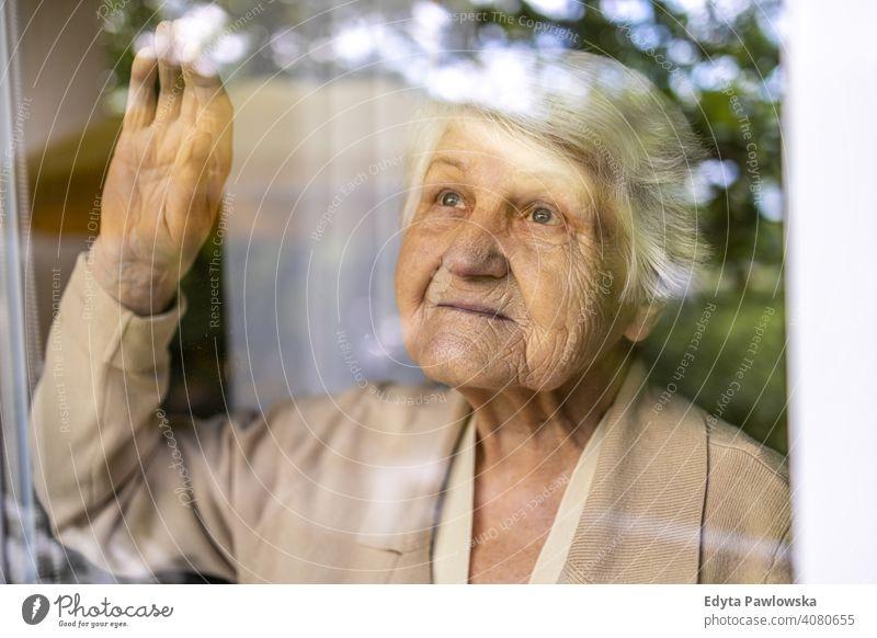 Ältere Frau schaut aus dem Fenster zu Hause traurig einsam unglücklich Depression Unsicherheit Angst beunruhigt Trauer Traurigkeit Verlust Problematik Krise