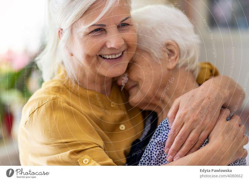 Frau, die ihre ältere Mutter umarmt Lächeln Glück genießend Positivität Vitalität Freude Selbstvertrauen Menschen Senior reif lässig Kaukasier heimwärts Haus