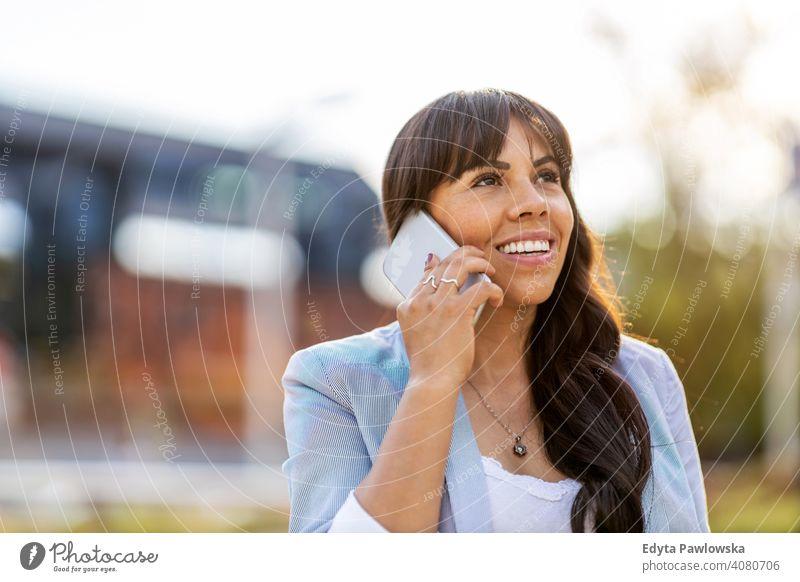 Attraktive junge Frau mit Smartphone in der Stadt hispanisch Latein Lächeln Sommer Spaß Freude Glück Fröhlichkeit Großstadt urban Mädchen Menschen Lifestyle