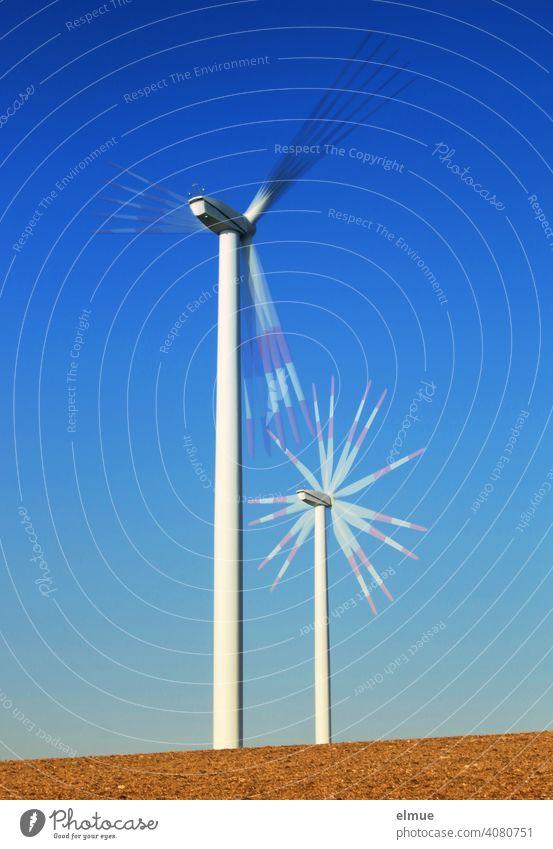 Zwei Windräder - Mehrfachbelichtung - auf einem Acker und vor blauem, wolkenlosen Himmel / alternative Stromerzeugung / Windkraft Windrad Drehung drehen Rotor