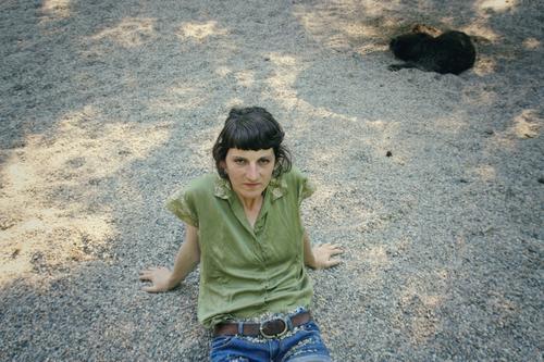 Frau sitzt auf Kiesboden lässig kies nachdenklich Identität reflektiert Gelassenheit feminin Pause Erde sitzen kritisch draußensein Einsamkeit Spielplatz Strand