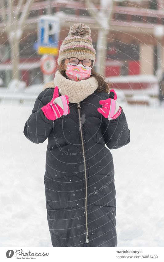 Porträt eines kleinen kaukasischen Mädchens mit einer Coronavirus-Maske und einer durch Schneefall beschlagenen Brille Unschuld Verantwortung Krankheit