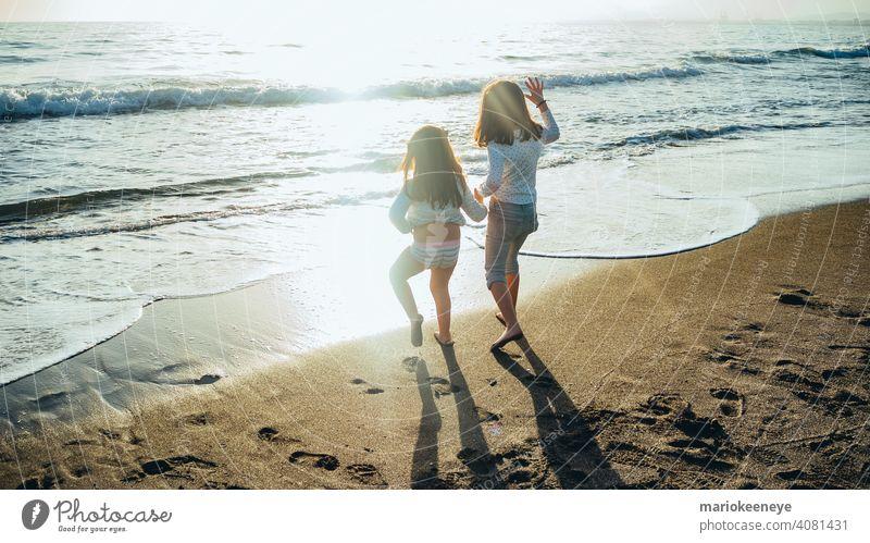 Rückenansicht von zwei kleinen Mädchen, die sich an einem sonnigen Nachmittag vor dem Meer an den Händen halten. Konzept der Freundschaft Zwei Personen