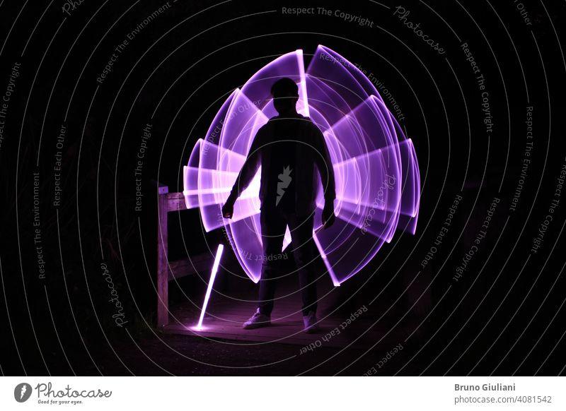 Silhouette eines Mannes stehend mit einem Lichtschwert mit Neon-Zeichnungen und Leds bei lightpainting Lichtmalerei Junge abstrakt Grafik u. Illustration