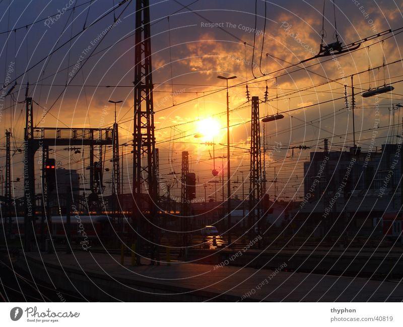 Sonnenuntergang am Bahnhof Oberleitung Draht Gleise München Verkehr Baugerüst