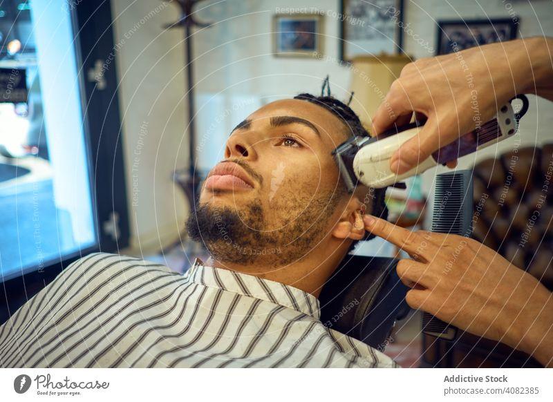 Anonymer Hairstylist beim Haarschnitt Friseur Kunde Pflege Friseursalon Trimmen Rasierer Mann Gesicht Behaarung Stil Spiegel Salon schwarz Afroamerikaner jung