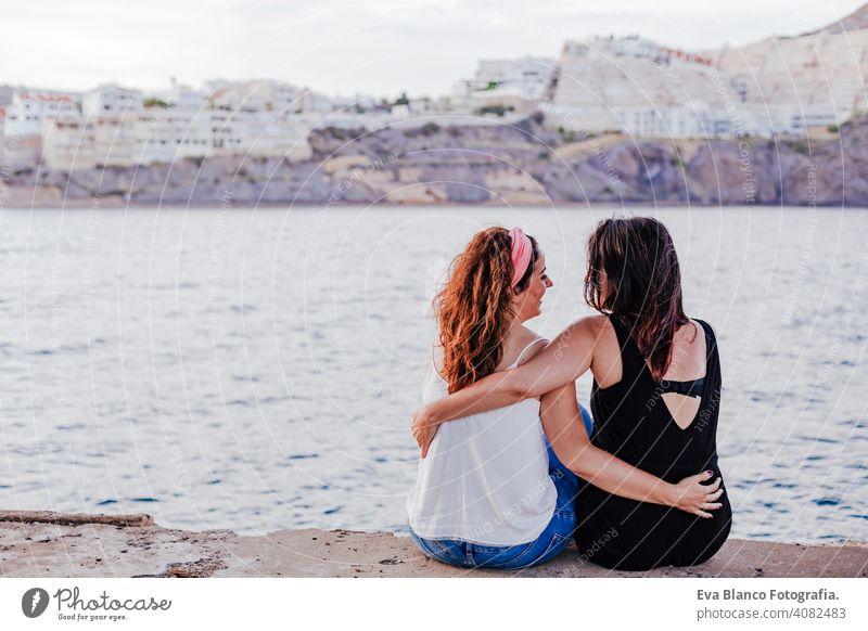 zwei Frauen Freunde sitzen am Strand umarmen. Lifestyle-Konzept im Freien lässig schwul urban heiter Freundin Stehen Paar jung Zuneigung Menschen Umarmen Jugend