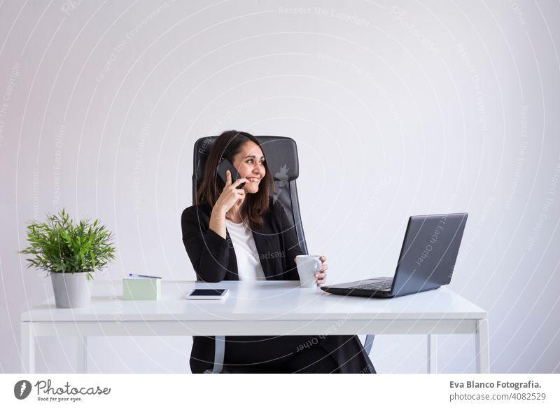 schöne junge Business-Frau mit seinem Laptop im Büro und sprechen über ihr Handy. Business Concept.white Hintergründe. Drinnen Computer Arbeiter Geschäftsfrau