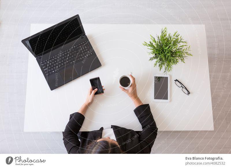 Draufsicht auf eine junge Geschäftsfrau, die im Büro mit Handy arbeitet und eine Tasse Kaffee hält. Tagsüber. Lebensstile. Innenbereich Frau Computer Laptop