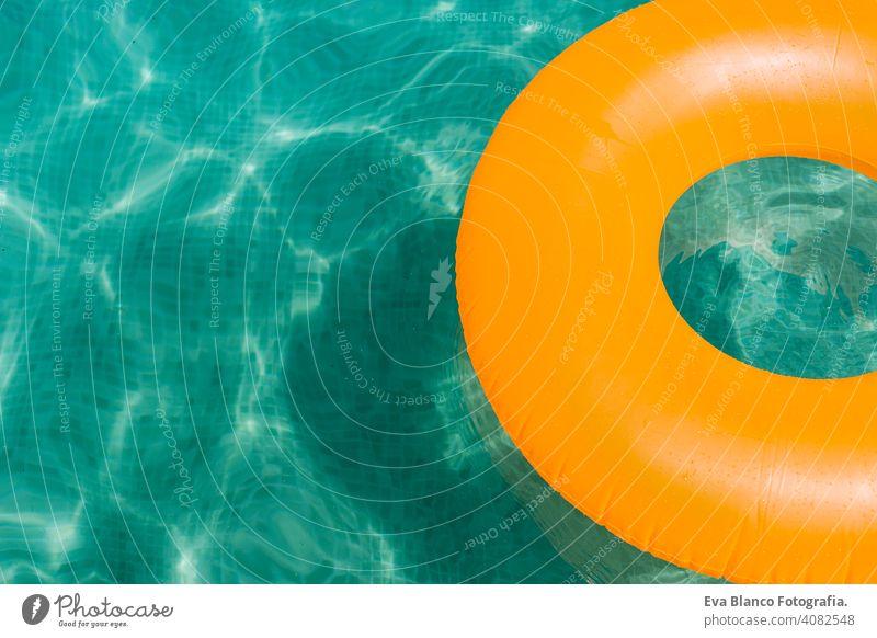 orange aufblasbaren Donut auf blauem Wasser in einem Schwimmbad. Sommer Spaß Pool Krapfen Party Sommerzeit schön Schwimmer Schwimmsport Frau Freizeit