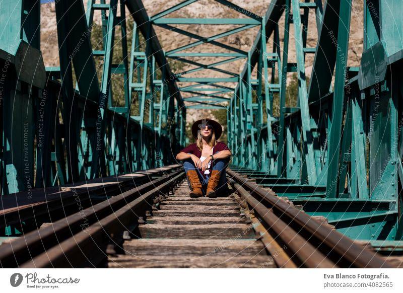 Porträt einer jungen schönen Frau, die auf der Eisenbahn einer grünen Brücke sitzt. Sie trägt stilvolle Kleidung und einen Hut. LIfestyle. Im Freien. Sonnig Zug