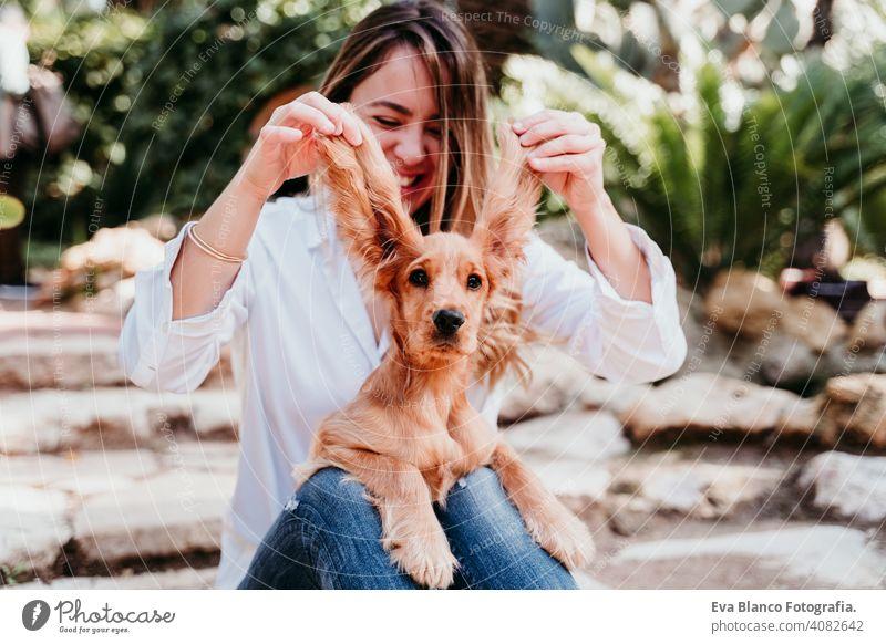 junge Frau und ihre niedlichen Welpen von Cocker Spaniel im Freien. Lustiger Hund große Ohren lustig Haustier Park sonnig Liebe Umarmung Lächeln Rückansicht