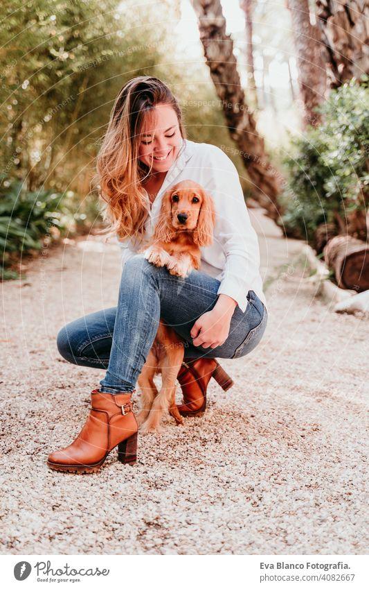 junge Frau und ihr niedlicher Cockerspaniel-Welpe im Freien in einem Park Hund Haustier sonnig Liebe Umarmung Lächeln Kuss züchten Reinrassig schön blond braun
