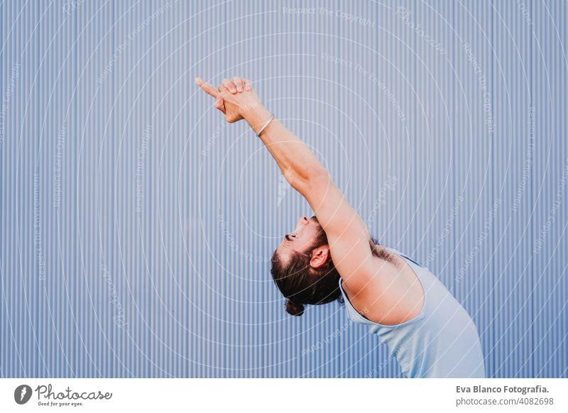 mann in der stadt, der yoga-sport betreibt. blauer hintergrund. gesunde lebensweise Blauer Hintergrund Yoga Mann Großstadt urban Lifestyle muskulös