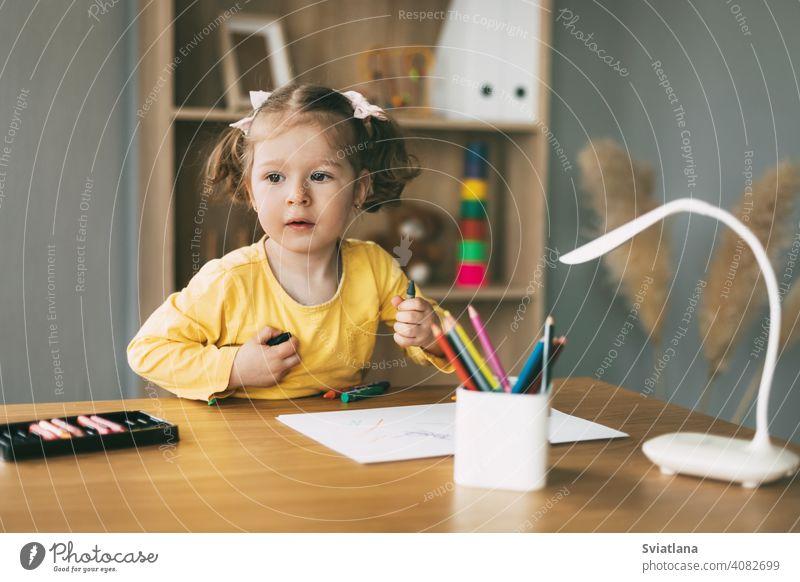 Ein kleines Mädchen zeichnet am Tisch mit Buntstiften zu Hause oder im Kindergarten. Kindheit, Kreativität, Bildung. zeichnen wenig Bleistift Papier niedlich