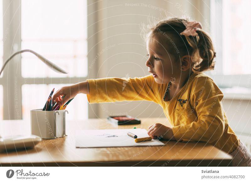 Ein kleines Mädchen zeichnet am Tisch mit Buntstiften zu Hause oder im Kindergarten. Kindheit, Kreativität, Bildung. Seitenansicht zeichnen wenig Bleistift