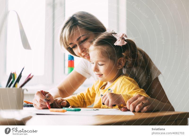 Eine junge Mutter bringt ihrer kleinen Tochter bei, mit Buntstiften zu zeichnen. Gemeinsame Zeit, Kreativität, Bildung. Seitenansicht Mädchen Kind Mama