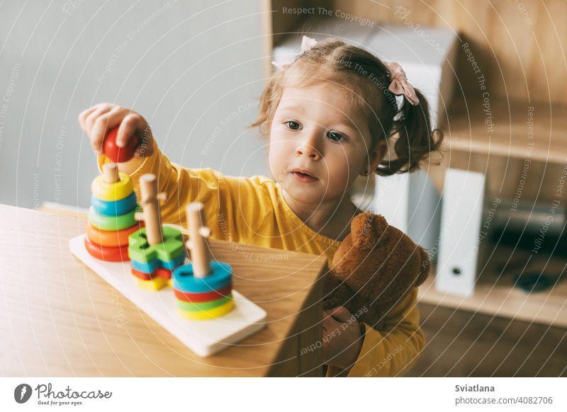 Ein kleines Mädchen sortiert bunte geometrische Formen. Entwicklung der motorischen Fähigkeiten. Entwicklung der motorischen Fähigkeiten und Styling von Figuren.
